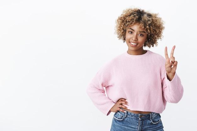 Foto de estúdio de uma mulher afro-americana confiante, despreocupada, relaxada e alegre, de aparência amigável, na casa dos 20 anos, mostrando o número dois fazendo pedidos sorrindo encantado posando sobre uma parede branca