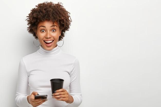 Foto de estúdio de uma mulher afro-americana satisfeita em trajes casuais, checando e-mail no celular