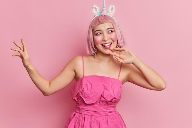 Foto de estúdio de uma mulher asiática alegre com um humor otimista, dançando despreocupada, levantando os braços, usando um vestido festivo, com um penteado bob