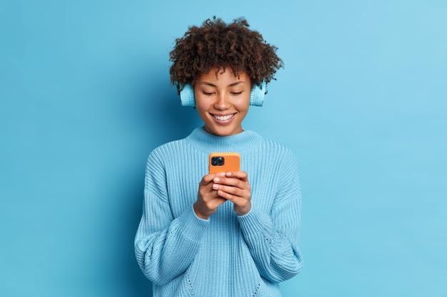 Foto de estúdio de uma mulher bonita, com cabelo encaracolado e sorriso largo, usa telefone celular para comunicação online, usa fones de ouvido estéreo, escolhe música para ouvir