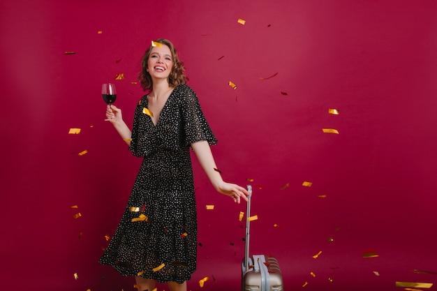 Foto de estúdio de uma mulher caucasiana alegre em um vestido longo vintage, degustando vinho