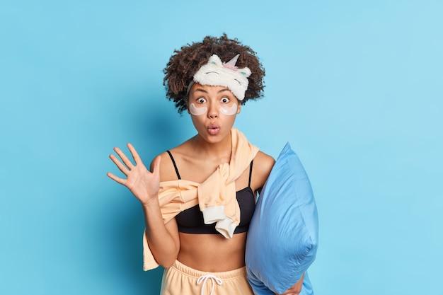 Foto de estúdio de uma mulher de cabelos cacheados impressionada levanta a palma da mão e olha para a câmera se preparando para dormir segura um travesseiro macio