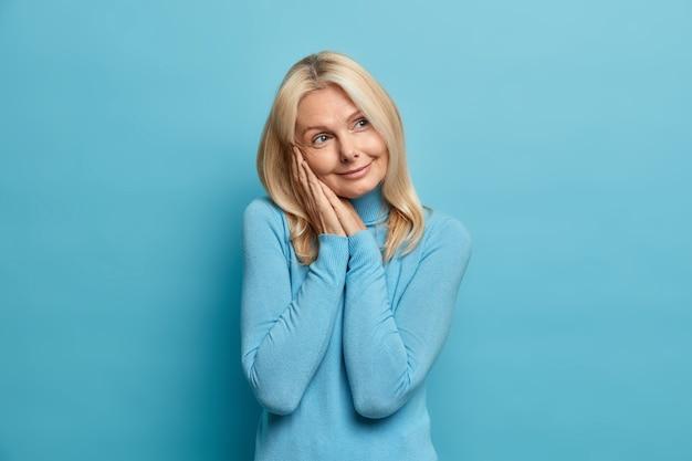 Foto de estúdio de uma mulher de meia-idade bem enrugada mantendo as mãos perto do rosto olhando pensativamente de lado com expressão sonhadora