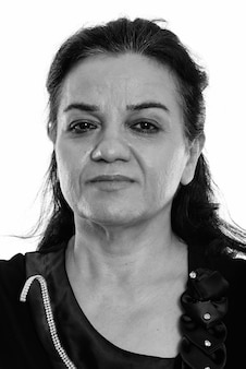 Foto de estúdio de uma mulher de negócios persa madura isolada contra um fundo branco em preto e branco