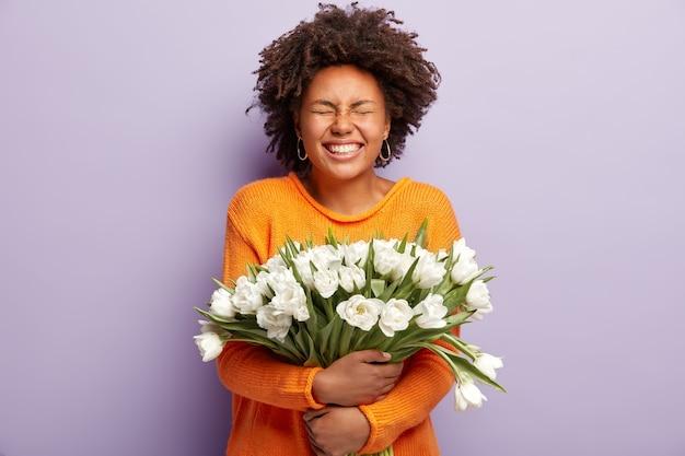 Foto de estúdio de uma mulher de pele escura radiante fecha os olhos de emoções positivas e sorri amplamente