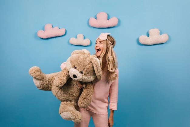 Foto de estúdio de uma mulher de pijama segurando um brinquedo
