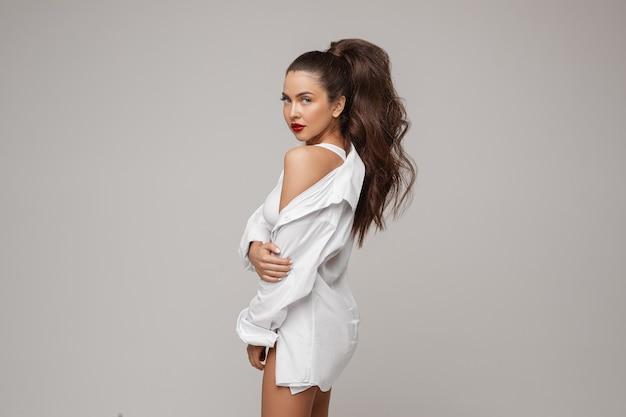 Foto de estúdio de uma mulher deslumbrante com cabelo escuro e abundante no rabo, vestindo uma camisa branca grande demais. ela tem lábios vermelhos brilhantes. olhando para a câmera. expondo o ombro nu para a câmera.
