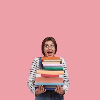 Foto de estúdio de uma mulher europeia alegre usando óculos redondos e segurando muitos livros