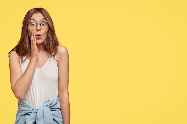 Foto de estúdio de uma mulher europeia emocionada e estupefata expressa admiração