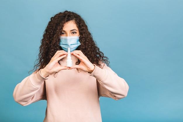 Foto de estúdio de uma mulher infectada com spray nasal nas mãos, senhora usando máscara protetora