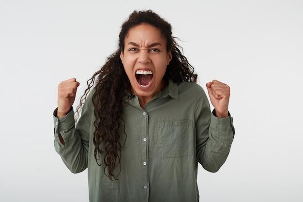 Foto de estúdio de uma mulher louca de cabelos compridos, morena, cacheada, levantando os punhos com entusiasmo enquanto grita de raiva, vestida com uma camisa verde enquanto posa sobre um fundo branco