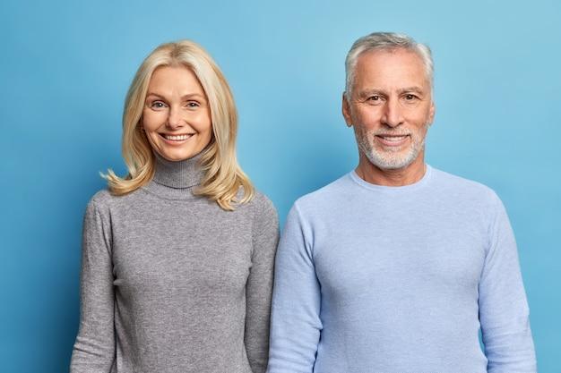 Foto de estúdio de uma mulher madura feliz e um homem expressam emoções positivas, aproveite a vida, espere pelas crianças que vêm vestidas com um casaco casual isolado na parede azul do estúdio