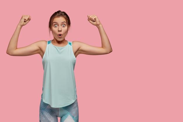 Foto de estúdio de uma mulher maravilhada mostrando o bíceps nas duas mãos