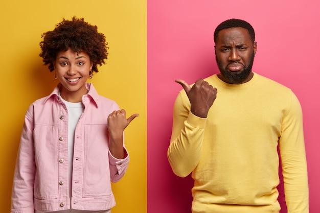 Foto de estúdio de uma mulher negra alegre e um homem barbudo sombrio apontando o polegar um para o outro, culpando e expressando emoções diferentes