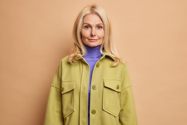 Foto de estúdio de uma mulher séria de meia-idade com uma pele saudável e bem cuidada olhando diretamente para a câmera com um mínimo de maquiagem