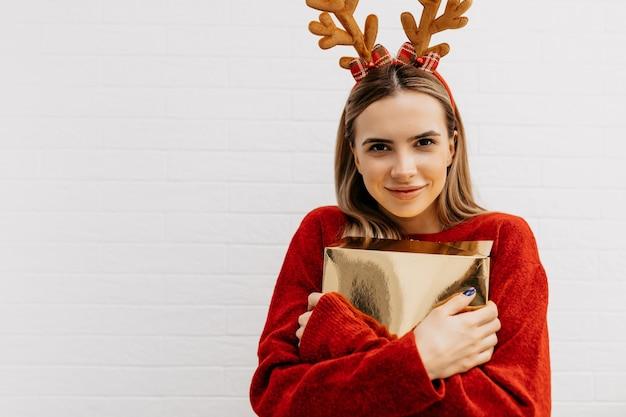 Foto de estúdio de uma senhora bonita encantadora de pulôver vermelho usando acessórios para a cabeça segurando um presente de ouro e se preparando para as férias Foto gratuita