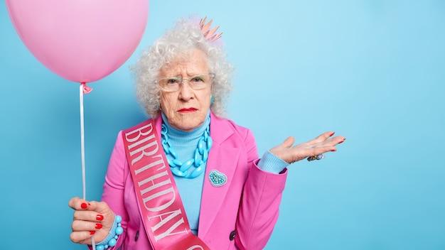 Foto de estúdio de uma senhora idosa enrugada de cabelos grisalhos levanta as palmas das mãos parece sério, vestida com roupas festivas segura um balão inflado comemora aniversário
