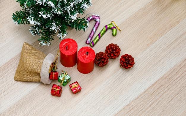 Foto de estúdio de vista de cima de itens decorativos de festival de véspera de natal pequena sacola cheia de caixas de presentes de presente velas vermelhas sementes de pinho mock up árvore de natal e vara de cana-de-doces na mesa de madeira com espaço de cópia.