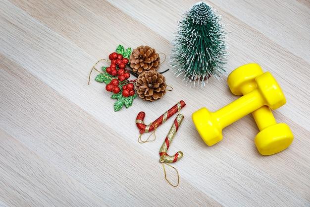 Foto de estúdio de vista superior da véspera de natal e itens decorativos do festival de ano novo pequena árvore de natal de maquete sementes de pinho cereja fruta bastões de cana de doces e halteres amarelos na mesa de madeira com espaço de cópia.