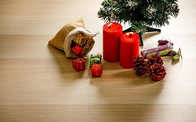 Foto de estúdio de vista superior de itens decorativos de festival de véspera de natal pequena sacola cheia de caixas de presentes de presente velas vermelhas sementes de pinho mock up árvore de natal e bastão de doces na mesa de madeira com espaço de cópia.