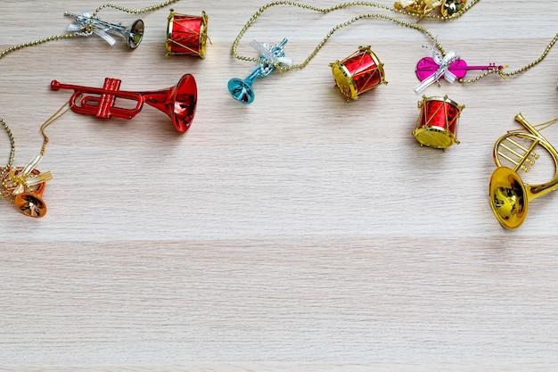 Foto de estúdio de vista superior de pequeno colorido brilhante simulado pendurado instrumentos musicais decorativos guitarra violino bateria trompete trombone em corda de prata e corrente de ouro na mesa de madeira marrom claro com espaço de cópia.