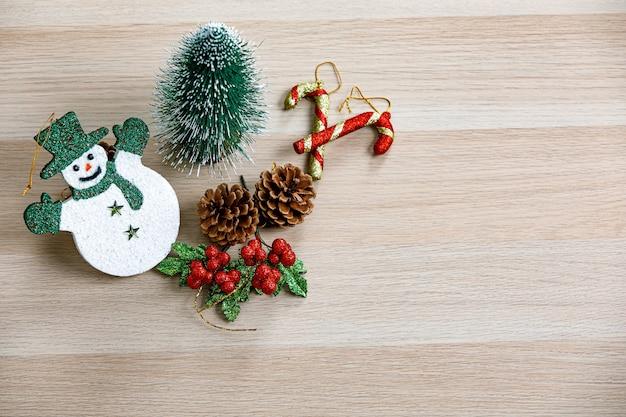 Foto de estúdio de vista superior do boneco de neve de rosto sorridente de itens decorativos de festival de véspera de natal com chapéu verde luvas e lenço pequeno mock up árvore sementes de pinheiro frutas cereja e bastões de bastão de doces na mesa de madeira.