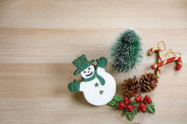 Foto de estúdio de vista superior do boneco de neve de rosto sorridente de itens decorativos de festival de véspera de natal com chapéu verde luvas e lenço pequeno mock up árvore sementes de pinho frutas cereja e bastões de cana-de-doces na mesa de madeira.