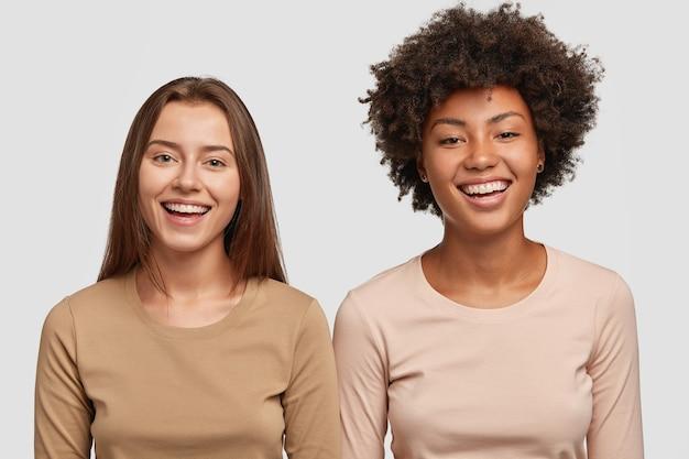 Foto de estúdio do atraente e alegre melhor amigo inter-racial de bom humor, um ao lado do outro e um sorriso largo