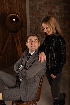 Foto de estúdio do belo casal jovem em pé perto um do outro e olhando para a câmera com um sorriso