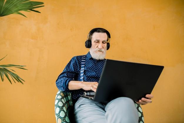 Foto de estúdio do homem sênior concentrado bonito em roupas elegantes, usando fones de ouvido, sentado na cadeira e usando o computador portátil