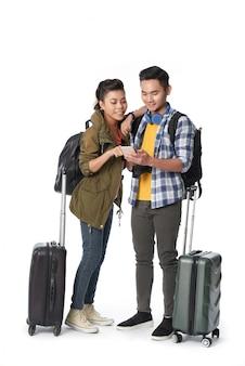 Foto de estúdio do jovem casal com bagagem, navegar na net em smartphone