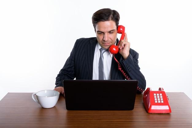 Foto de estúdio do jovem empresário persa falando no telefone antigo