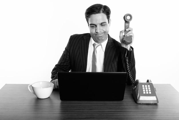 Foto de estúdio do jovem empresário persa sentado atrás de uma mesa de madeira, isolado, preto e branco