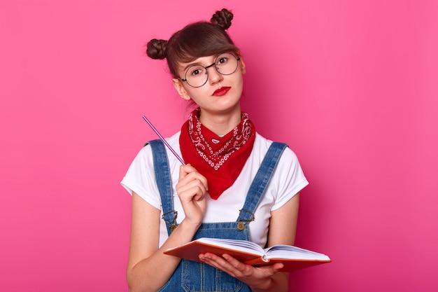 Foto de estúdio do jovem estudante pensativo pensativo com batom vermelho no rosto