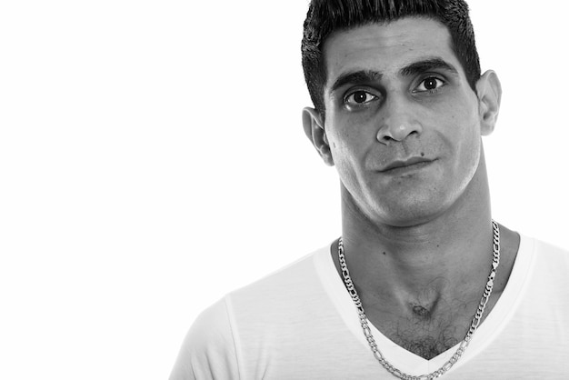 Foto de estúdio do jovem persa isolado contra um fundo branco em preto e branco