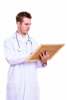 Foto de estúdio do médico lendo na placa de madeira