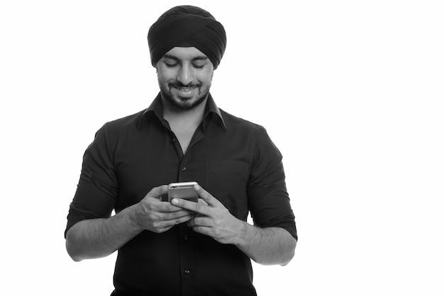 Foto de estúdio em preto e branco de um jovem empresário sikh indiano barbudo com turbante isolado contra um fundo branco