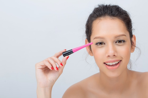 Foto de estúdio indoor para linda mulher caucasiana, sorrindo amplamente aplicando rímel preto nas pestanas