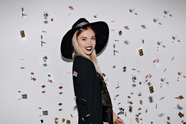 Foto de estúdio interno da incrível modelo feminina em roupa preta sorrindo