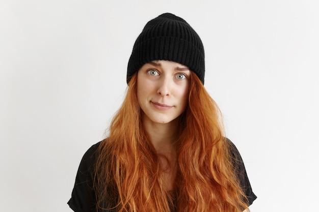 Foto de estúdio interno de garota ruiva fofa hippie vestindo camiseta e chapéu com olhar indignado e culpado