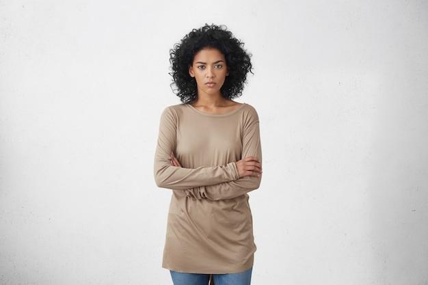 Foto de estúdio interno de uma jovem dona de casa de pele escura com roupas casuais