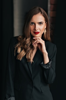 Foto de estúdio interno de uma mulher bonita e atraente com cabelo castanho claro e jaqueta preta com lábios vermelhos