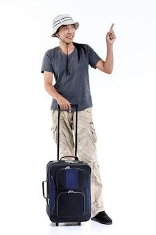 Foto de estúdio isolada de asiático feliz cabelo comprido rabo de cavalo masculino aventura viajante em pé apontando no espaço em branco para anúncios segurando o carrinho de bagagem de viagem para férias de férias em fundo branco.
