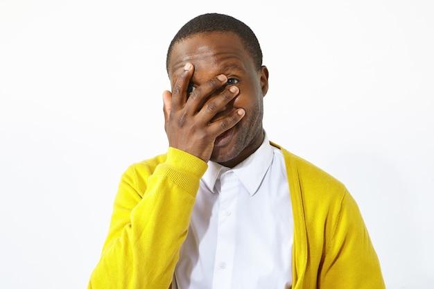Foto de estúdio isolada de atraente jovem afro-americano em roupas elegantes, cobrindo o rosto com a palma da mão, rindo de situação ridícula engraçada. linguagem corporal, expressões humanas, gestos e sinais