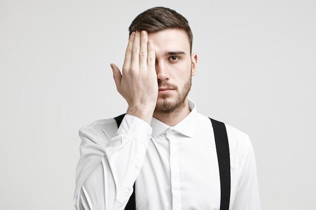 Foto de estúdio isolada de jovem e bonito trabalhador corporativo com cabelo eriçado e estiloso, olhando para a câmera, cobrindo um olho com a palma da mão, como se tivesse seus olhos testados durante o exame de visão