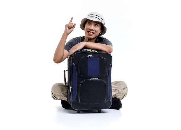Foto de estúdio isolada de viajante asiático feliz aventura masculina usar chapéu de balde sentado sorrindo, abraçando segurando a bagagem de viagem do carrinho apontando no espaço em branco para anúncio de texto no fundo branco.