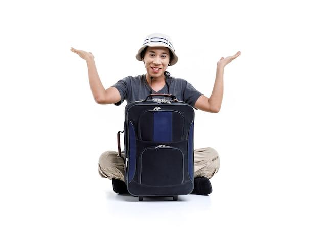 Foto de estúdio isolada do viajante asiático feliz aventura masculina usar chapéu de balde sentado sorrindo, abraçando segurando a bagagem de viagem do carrinho apontando no espaço em branco para anúncio de texto no fundo branco.