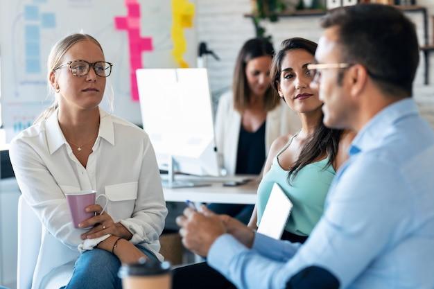 Foto de executivos casuais de várias idades trabalhando e conversando sobre o novo projeto juntos no escritório.