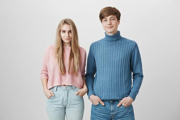Foto de família de caucasiano irmão e irmã em pé perto um do outro posando dentro de casa em camisolas de malha coloridas