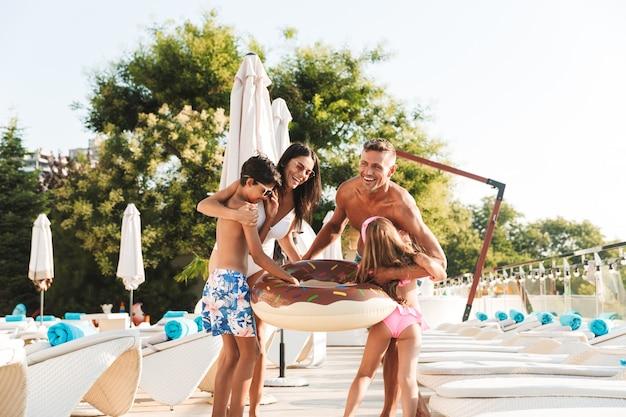 Foto de família feliz com crianças descansando perto de uma piscina luxuosa e se divertindo com um anel de borracha fora do hotel